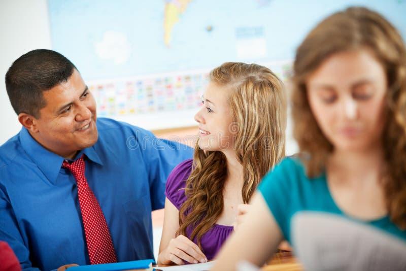 Middelbare school: Spaanse Leraar Helping Student stock afbeeldingen