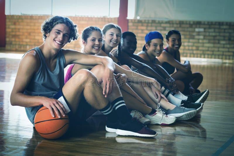 Middelbare schooljonge geitjes die op de vloer in basketbalhof binnen zitten stock afbeeldingen