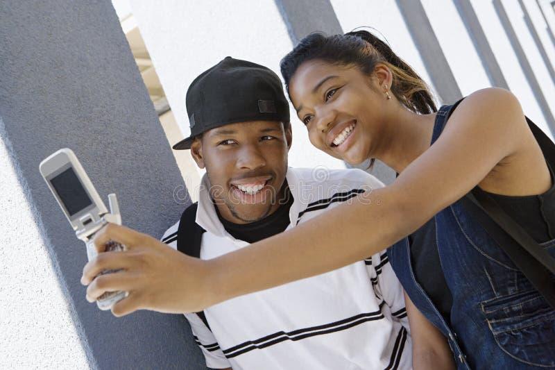 Middelbare schoolpaar die Zelfportret nemen stock fotografie