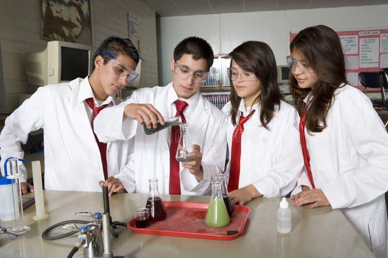 Middelbare schoolstudenten die Wetenschapsexperiment leiden stock foto's