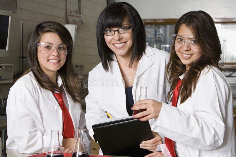Middelbare schoolstudenten met Professor In Chemistry Lab stock afbeelding