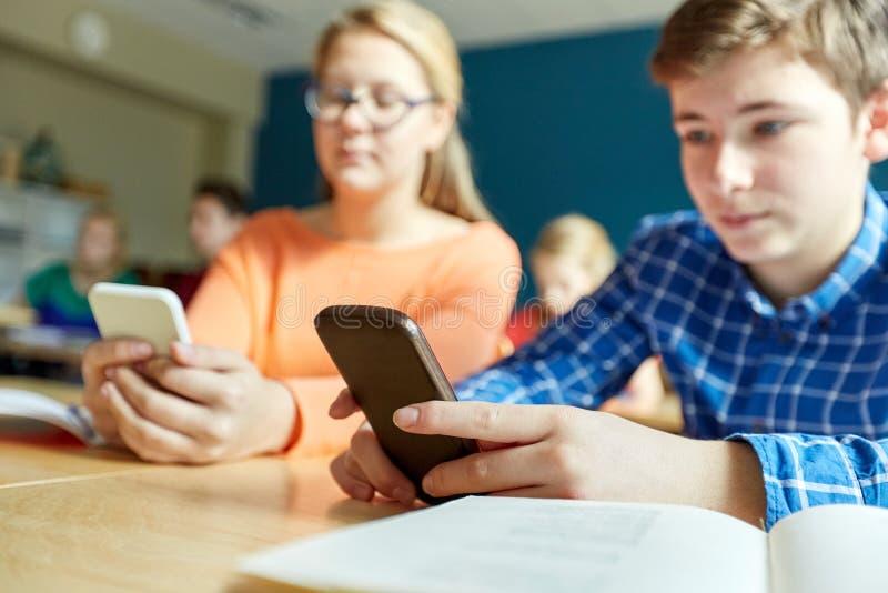 Middelbare schoolstudenten met smartphones het texting royalty-vrije stock afbeeldingen