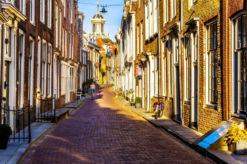 Dutch biker at Sunset in Narrow Streets in the Historic City of Middelburg in Zeeland Province, the Netherlands royalty free stock photo