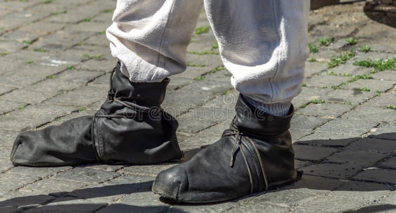 Middeleeuwse die broeksbandschoenen van zachte zwarte leerstrepen worden gemaakt over een lichtgrijze linnenbroeken royalty-vrije stock afbeelding