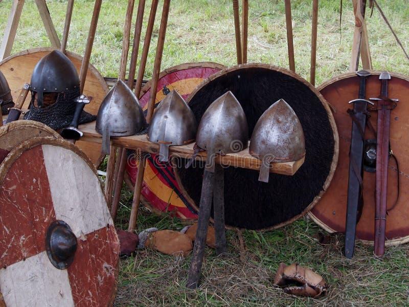Middeleeuwse dorp, helmen en wapens van de Vikingen, de zwaarden en de schilden stock foto's