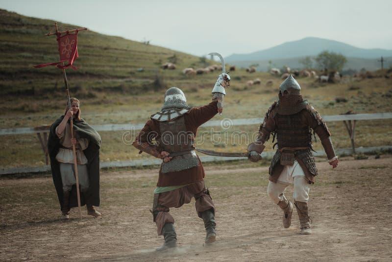 Middeleeuwse joust ridders in helmen en de slag van de kettingspost op zwaard stock afbeelding