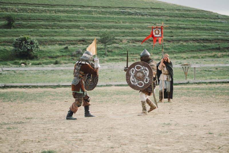 Middeleeuwse joust ridders in helmen en de slag van de kettingspost op zwaard stock fotografie