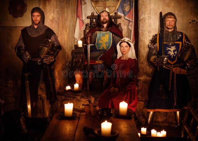 Middeleeuwse koning met zijn koningin en ridders op wacht in kasteelbinnenland stock foto's