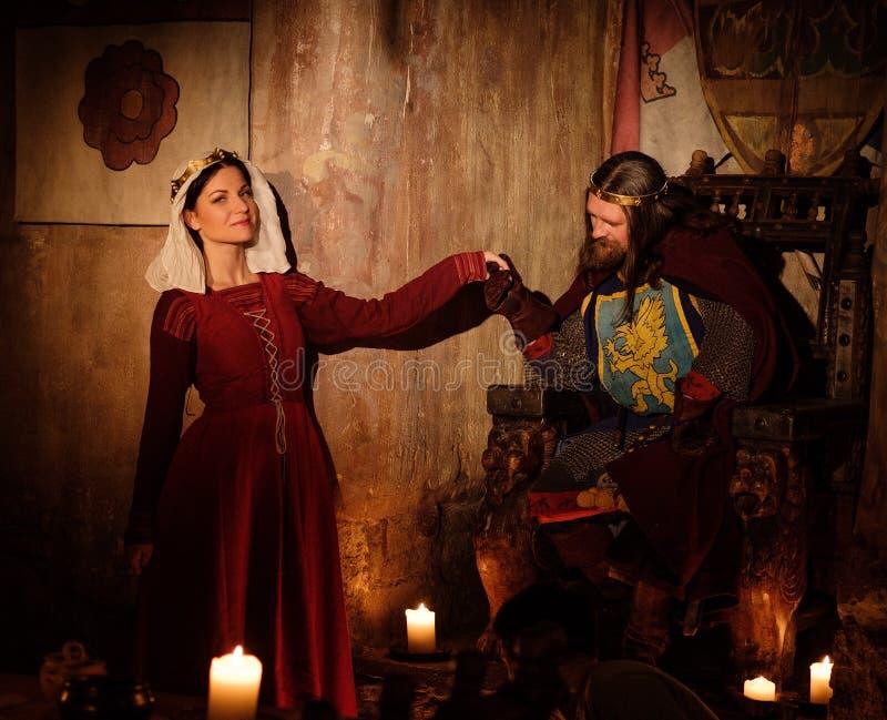 Middeleeuwse koning met zijn koningin in oud kasteelbinnenland royalty-vrije stock afbeeldingen