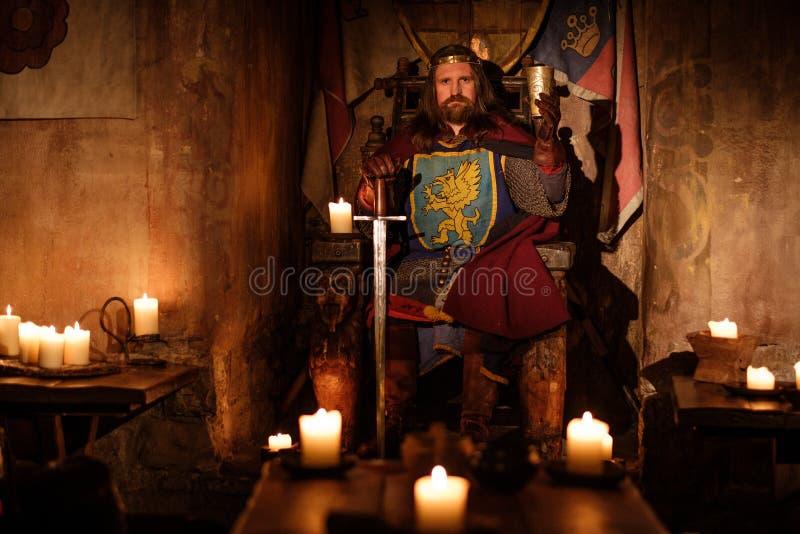 Middeleeuwse koning op troon in oud kasteelbinnenland stock afbeelding