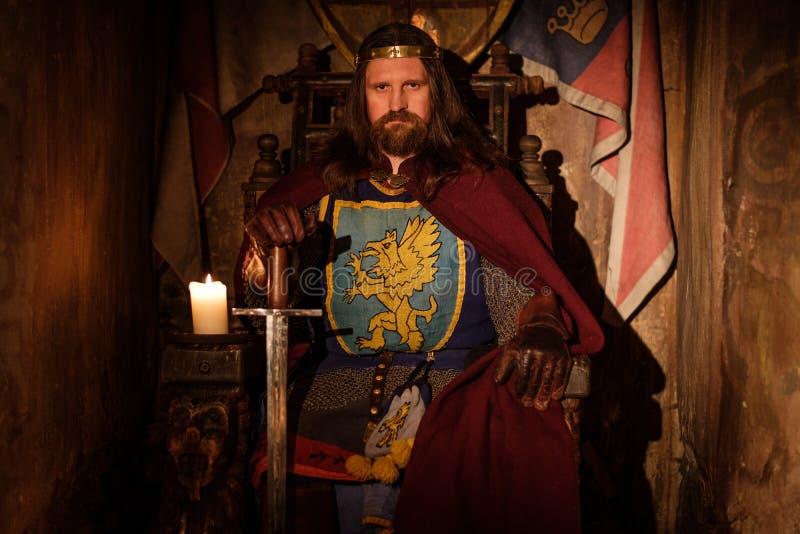 Middeleeuwse koning op troon in oud kasteelbinnenland royalty-vrije stock foto's