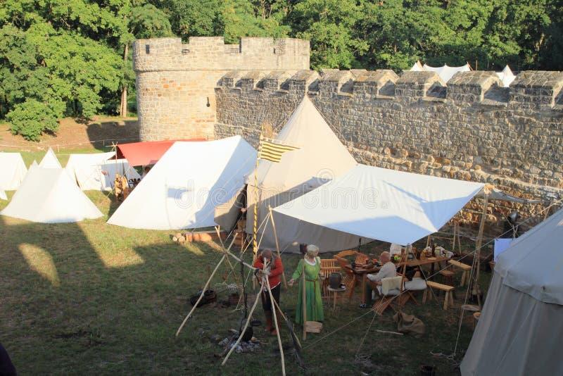Middeleeuwse militairen en vrouw in historisch kamp op Kasteel Budyne stock foto's