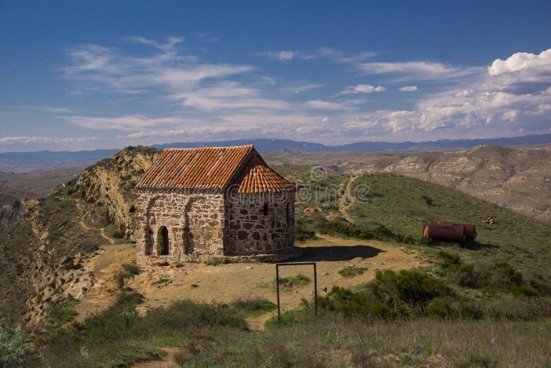 Middeleeuwse orthodoxe kapel op heuveltop van Georgische berg stock afbeeldingen