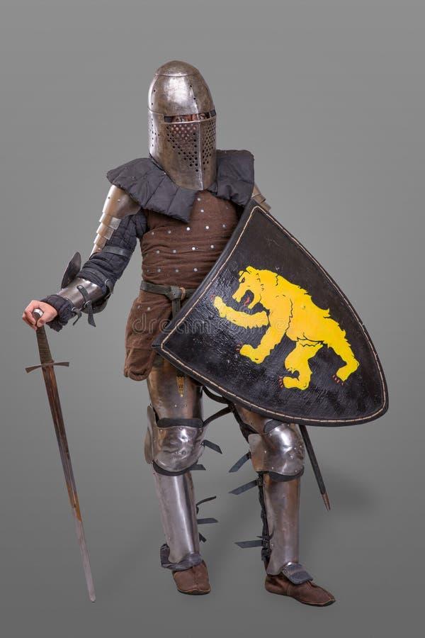 Middeleeuwse ridder met Zwaard, Schild, Helm tegen grijze achtergrond royalty-vrije stock foto's