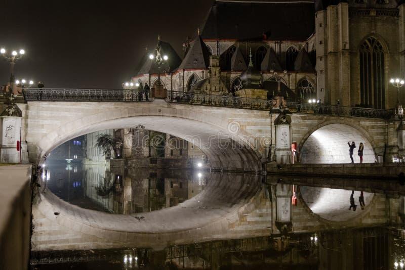 Middeleeuwse steenbrug die in een stadskanaal bij nacht nadenken stock fotografie