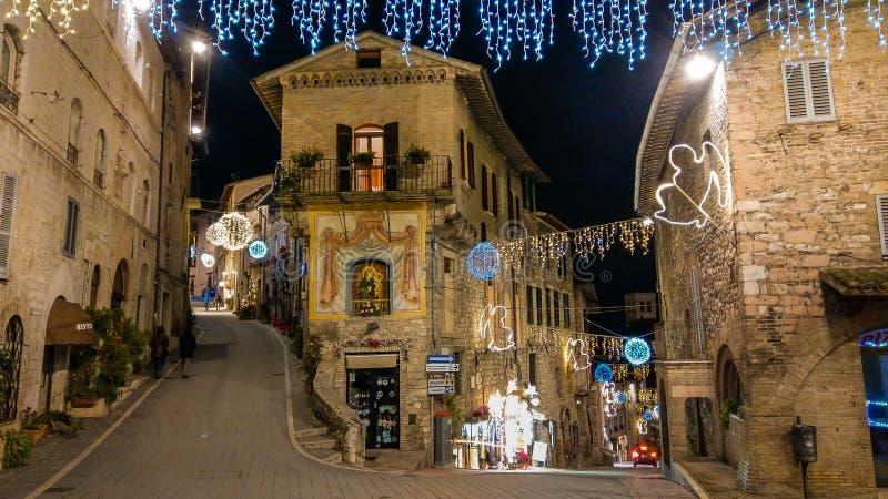Middeleeuwse straat van Assisi met Kerstmisdecoratie bij de winternacht, Umbrië royalty-vrije stock fotografie