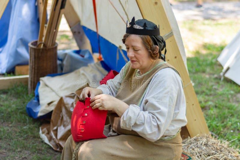 Middeleeuwse vrouw in traditionele kostuums voor een tent die een rode hoed naaien bij het ridderfestival royalty-vrije stock foto's