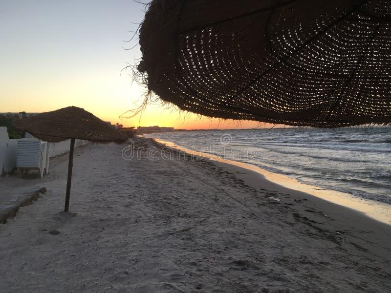 Middellandse Zee, strand, zonsondergang, rieten paraplu's en golven stock afbeelding