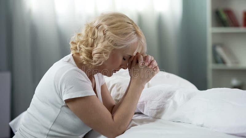 Midden-leeftijdsdame bidden, die op de vloer dichtbij bed, geloof en hoop, godsdienst zitten royalty-vrije stock afbeeldingen