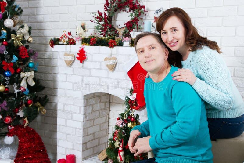Midden oud paar in de de Kerstmisruimte, open haard van het Nieuwjaar en de Kerstboom, houdende van familie stock afbeelding
