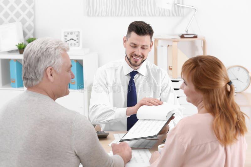 Midden oud paar die contract ondertekenen bij verzekeringsagentschap stock foto's