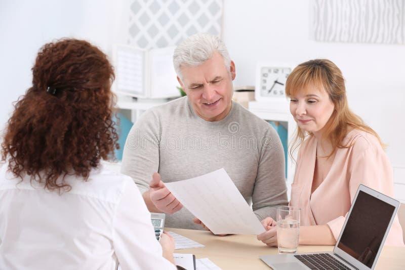 Midden oud paar die contract ondertekenen bij verzekeringsagentschap stock afbeeldingen