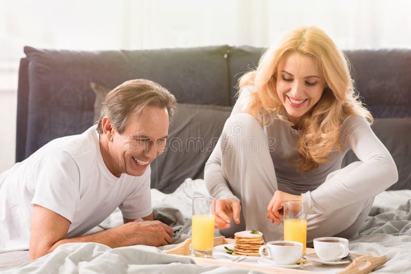 Midden oud paar die pannekoeken samen in bed eten royalty-vrije stock foto's