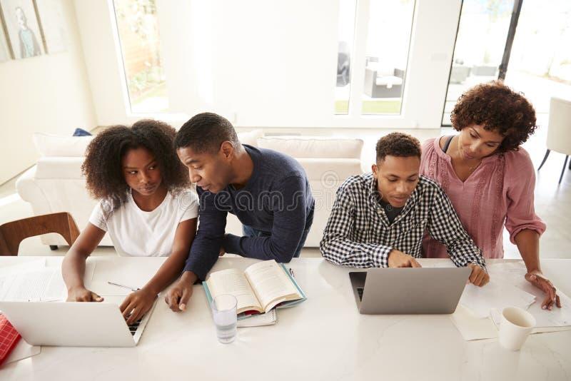 Midden oude Afrikaanse Amerikaanse ouders die hun tienerjonge geitjes helpen gebruikend laptops om thuiswerk, opgeheven mening te royalty-vrije stock fotografie