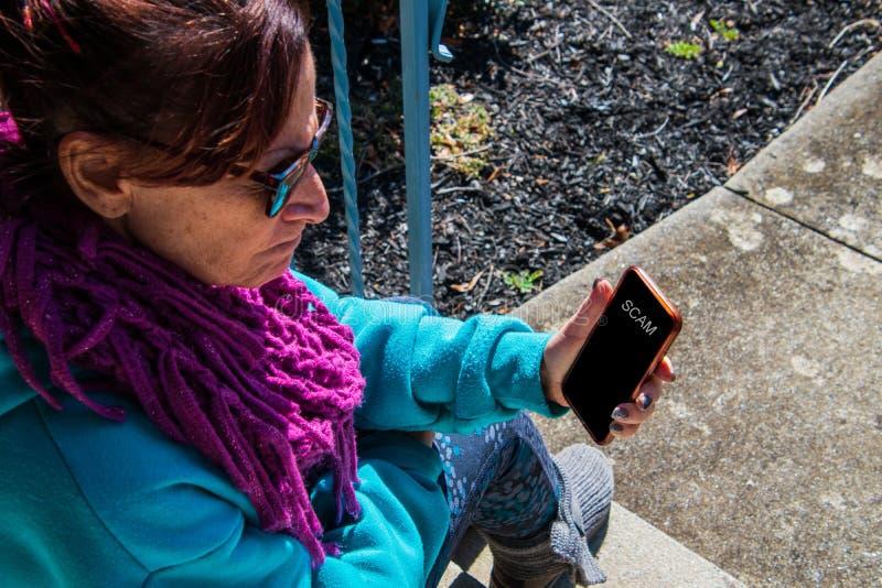 Midden oude baby boomer Kaukasische vrouw die bekijkend haar telefoon met woede kijken Het scherm van de celtelefoon zegt zwendel royalty-vrije stock afbeeldingen