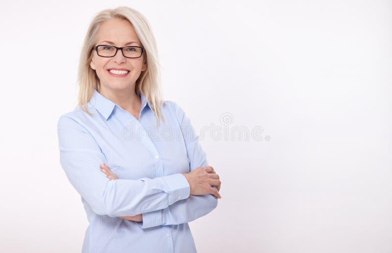 Midden oude bedrijfsvrouw met oogglazen in blauw die overhemd op witte achtergrond wordt geïsoleerd royalty-vrije stock afbeeldingen