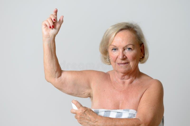 Midden Oude Dame Applying Deodorant op Oksel royalty-vrije stock afbeelding