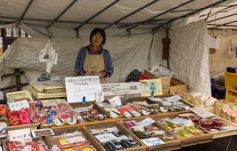 Midden oude Japanse vrouwelijke verkoper op straatmarkt royalty-vrije stock afbeelding