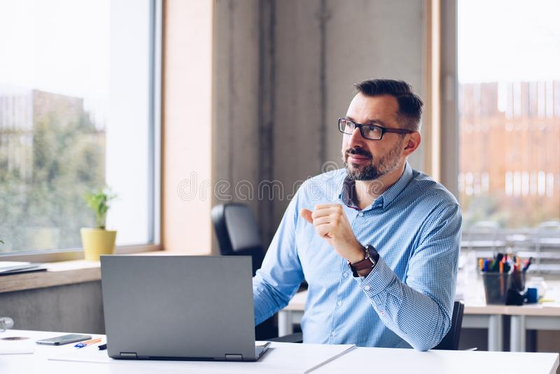 Midden oude knappe mens in overhemd die aan laptop computer in bureau werken stock foto