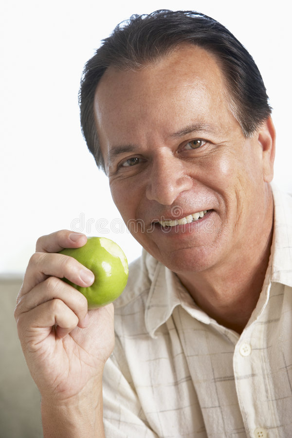 Midden Oude Mens die Groene Appel en het Glimlachen eet stock fotografie