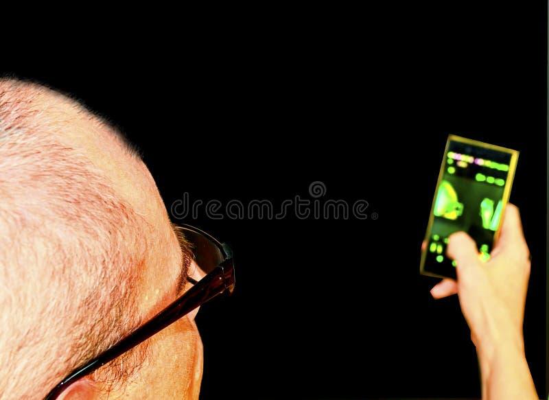Midden oude mens die met glazen in een leunstoel zitten Rijpe mens met mobiele telefoon op zwarte achtergrond De ruimte van het e stock foto