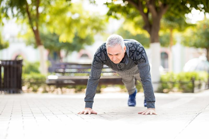 Midden oude mens die opwarmingsoefening in het park doen stock afbeelding