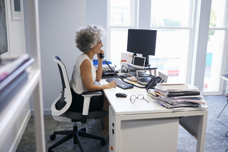 Midden oude onderneemster die de telefoon in haar bureau met behulp van stock afbeelding