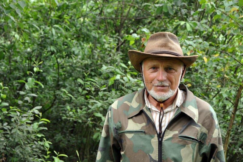 Midden oude reiziger Portret van een knappe volwassen mens met een grijze baard en hoed in camouflagekleding stock foto's