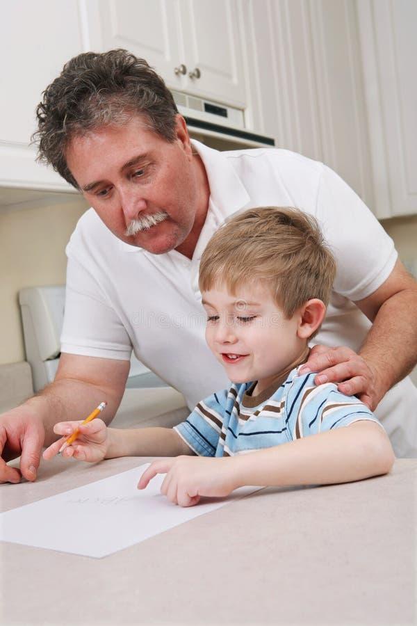 Midden oude vader die jonge zoon met thuiswerk helpt royalty-vrije stock afbeeldingen