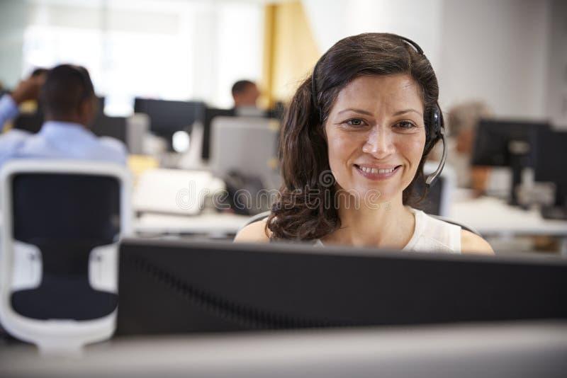 Midden oude vrouw die bij computer met hoofdtelefoon in bureau werken stock fotografie