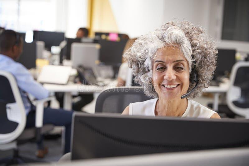 Midden oude vrouw die bij computer met hoofdtelefoon in bureau werken stock afbeelding