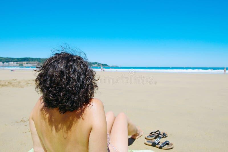 Midden oude vrouw die bij strand dichtbij het overzees rusten stock foto