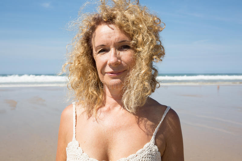 Midden oude vrouw die bij strand dichtbij het overzees rusten stock fotografie