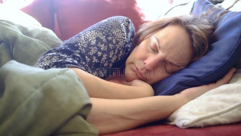 Midden oude vrouw die op een rode laag onder een groene deken in de loop van de dag dutten royalty-vrije stock foto
