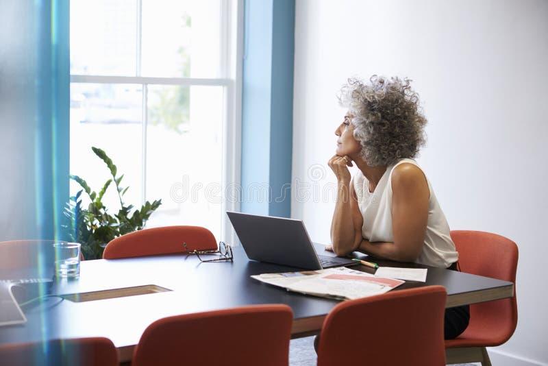 Midden oude vrouw die uit het venster in de bestuurskamer kijken royalty-vrije stock foto