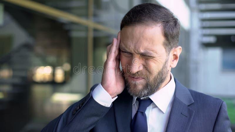 Midden oude zakenman die aan sterke hoofdpijn, zware baan, bezige levensstijl lijden royalty-vrije stock afbeelding
