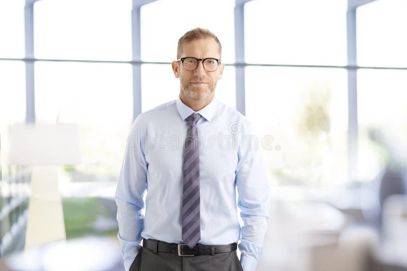 Midden oude zakenman op het kantoor stock fotografie