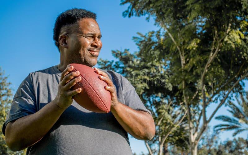 Midden oude zwarte mens die een voetbal vangen royalty-vrije stock afbeelding