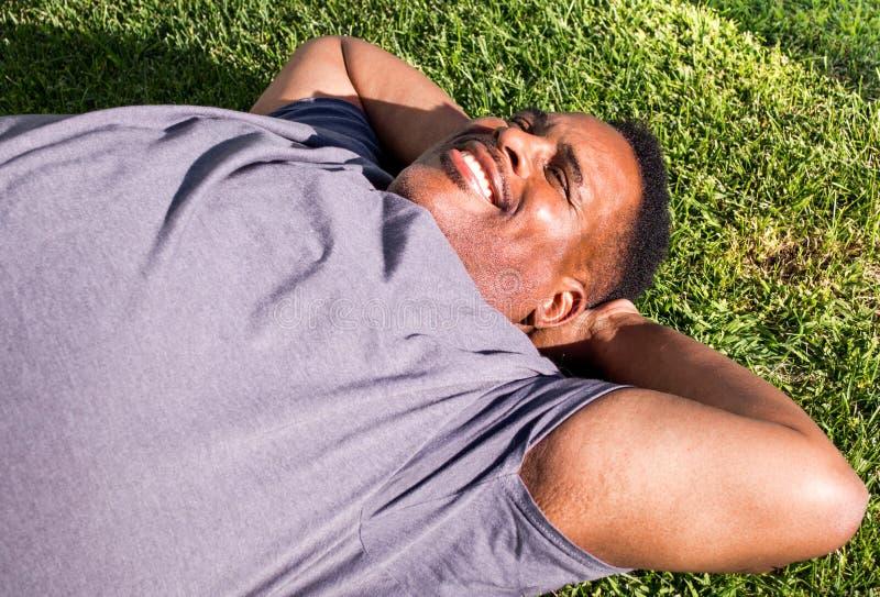 Midden oude zwarte mens die op het gras leggen stock fotografie