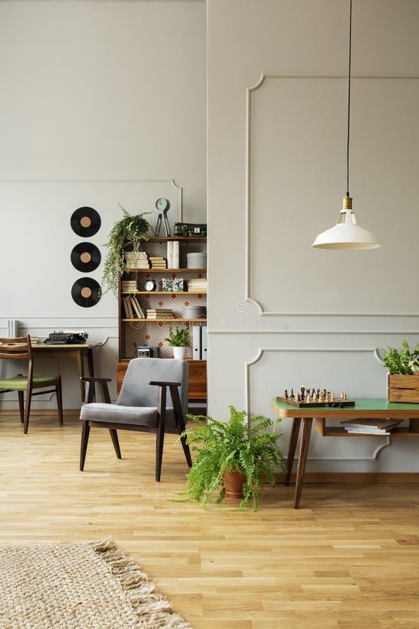 Midden van de eeuw moderne leunstoel in een grijs woonkamerbinnenland met houten meubilair, werkruimte en uitstekend decor Echte  stock foto